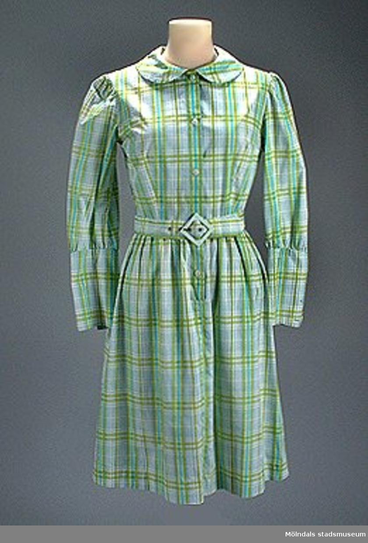 Flickklänning, sydd i blå- och grönrutigt bomullstyg. Klänningen är knäppt framtill, har rundad krage och ärmarna har långa manchetter. Rynkad kjol. Längd: 970 mm, axelbredd 360 mm, armlängd 570 mm, vidd 1420. MM03618_1.Skärp med ljusgrönt spänne 790 mm. MM03618_2.