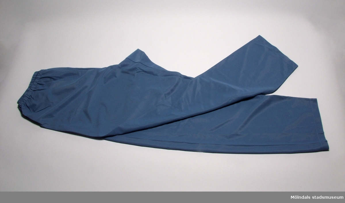 Pyjamasjacka i blågrå charmeusenylon.Längd: 710 mm, axelbredd: 470 mm, armlängd: 600 mm.Hör ihop med byxa MM 03633:2 och plastpåse MM 03633:3.Givaren Vanja Löfgren utbildade sig vid Stockholms tillskärarakademi i Göteborg 1950.Arbetade därefter först som biträdande föreståndarinna och sedan som föreståndarinna vid Eiser under tiden 1/11-1950- 31/8-1971, och ritade där bl. a. mönster.