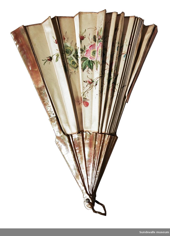 Solfjäder tillverkad av gräddfärgat siden med målade nyponrosor och stomme av pärlemor. Metallögla.