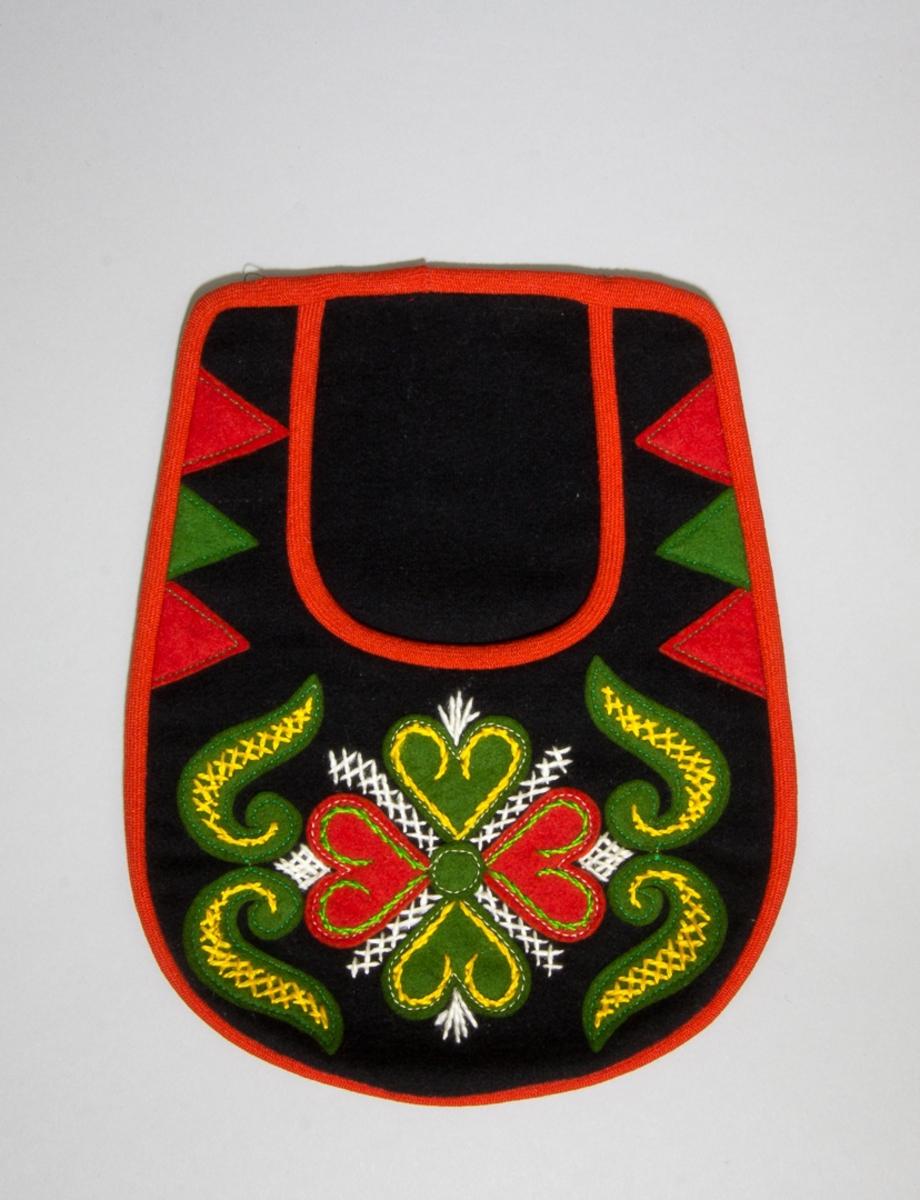 Kjolsäck till dräkt för kvinna från Leksands socken, Dalarna. Modell med u-formad öppning för handen. Tillverkad av svart ylletyg, kläde, med applikationer av kläde i rött och grönt, fastsydda på maskin med grön och vit tråd. Centralt placerad hjärtblomma med slingor vid sidan och trekanter efter kanterna. Broderi utfört med silke- eller konstsilkegarn i vitt, gult och grönt: flätsöm, sticksöm och stjälksöm. Framstycket fodrat med fabriksvävt bomullstyg, blårandigt, tuskaft. Kantad runtom med rött, diagonalvävt ylleband. Baksida av svart kläde.