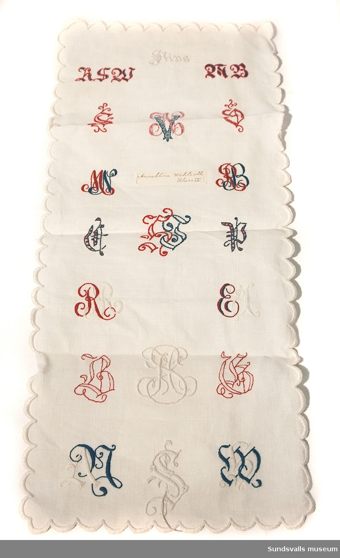 Tunt vitt linne med ett flertal olika exempel på monogram, broderade i rött, vitt, blått