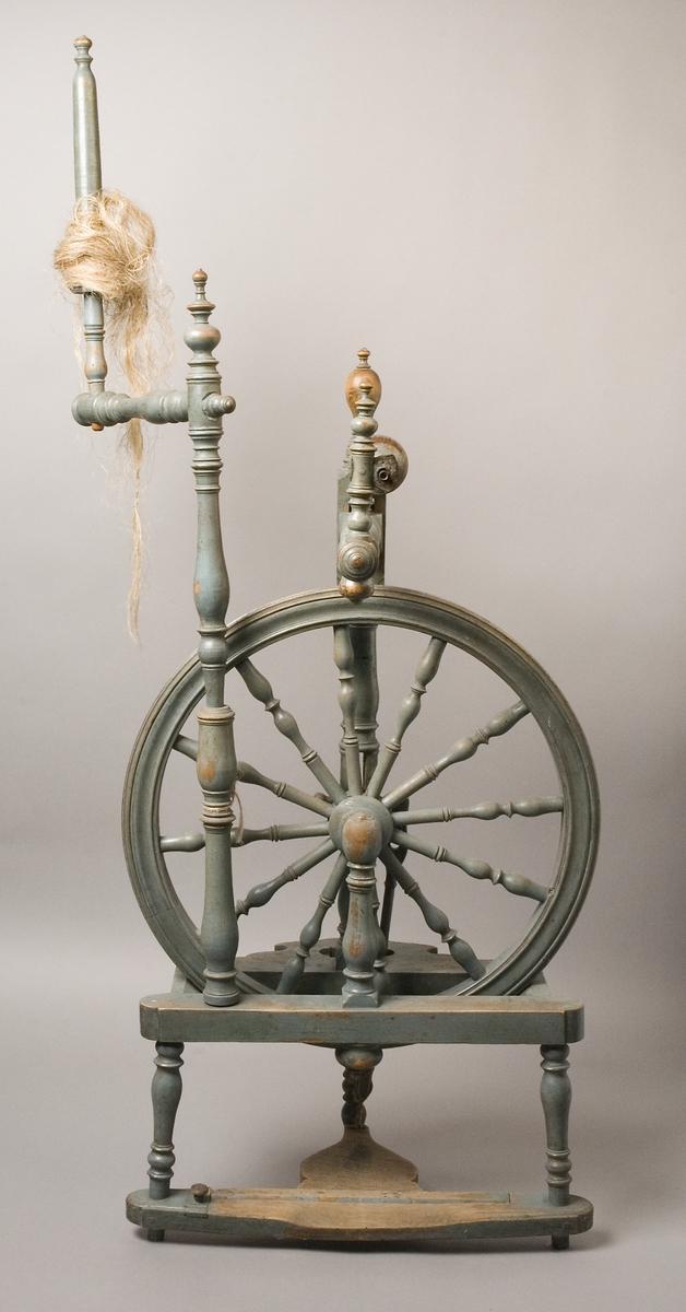 Spinnrock av bemålat trä. Överst svarvat linfäste som sitter på ett eget mindre fäste, insatt vinkelrätt i ståndare ned mot pall. Pallen har tre svarvade ben. I ramen/sargen för pallen finns fästen för svarvade ståndare, som håller hjulaxeln. Hjul med svarvade ekrar.