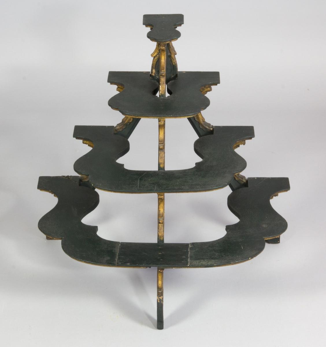 Liten hylla på tre ben med mjukt rundade hyllplan. Mörkgrön till färgen med guldbronserade kanter och ornament.