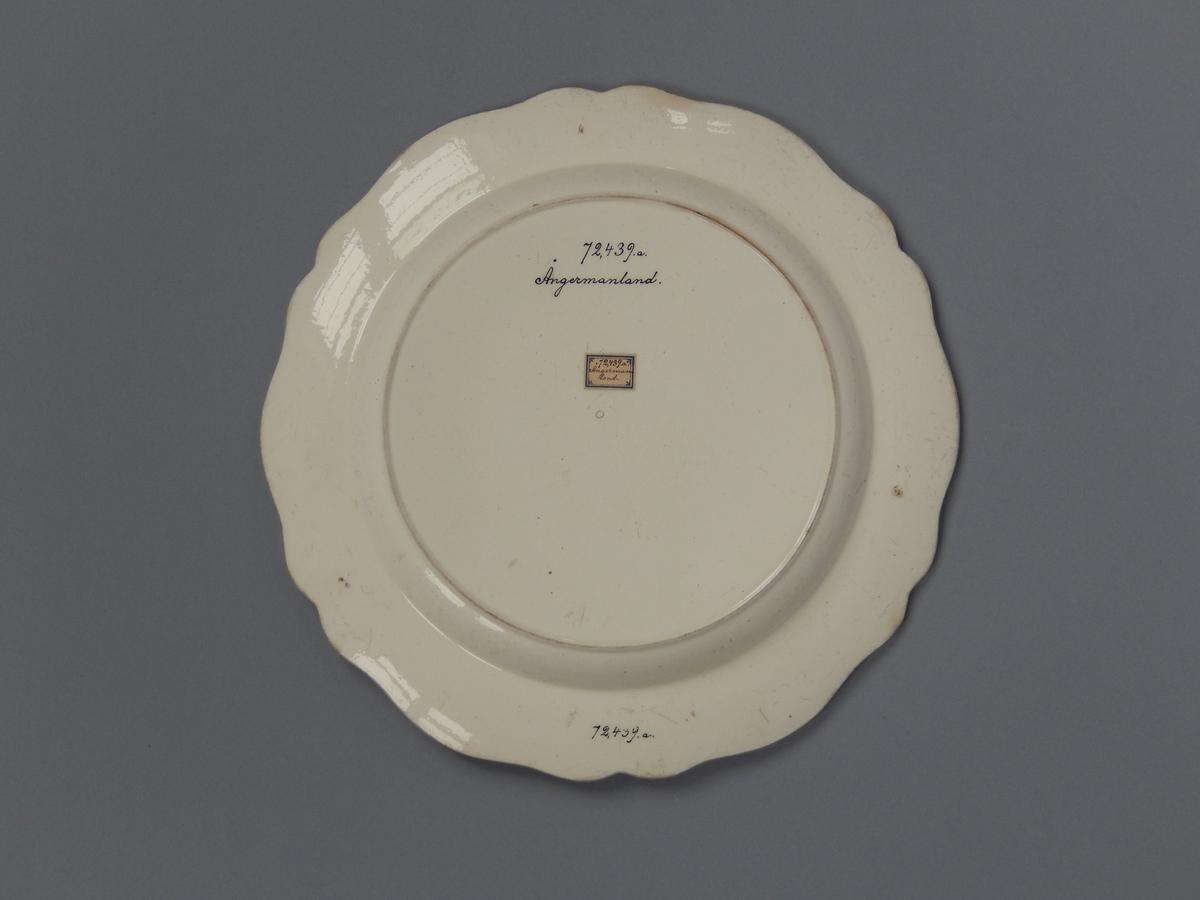 Tallrik, flat, av gulvitt glaserat flintgods med passformigt brätte. Rokokostil. Tallrikens yta nött.