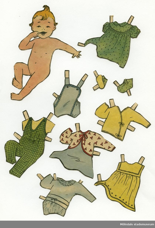 """Pappersdocka med kläder och tillbehör, urklippta ur tidning på 1950-talet. Docka och kläder är märkta """"Susanne"""" på baksidan - dockans namn.Dockan föreställer ett naket spädbarn med blont hår. Garderoben består av tre klänningar, fyra lek- och sparkdräkter i olika modeller, kofta, dopklänning, sockar, samt en overall. Dockan har också tillbehör, som en babylift och en hakklapp.Docka och kläder förvaras i ett litet vitt kuvert med texten """"Susanne"""" påtejpat på framsidan."""