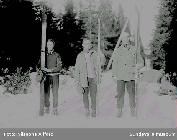 Tre män som står i skidspåret och visar upp sina skidor. Människor sitter bredvid skidspåret i bakgrunden.