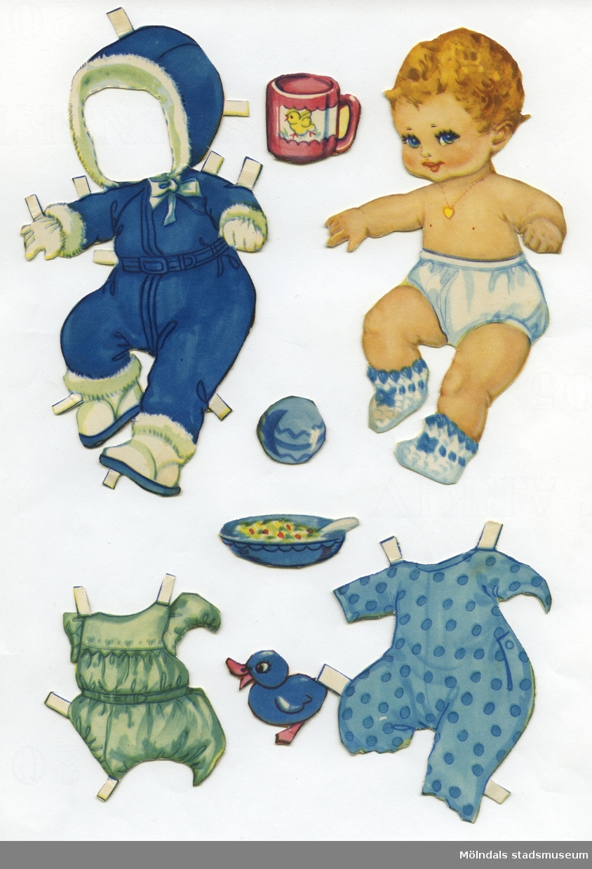 """Pappdocka med kläder och tillbehör från 1950-talet (E.O. & Co., nr 5538). Docka och kläder är märkta """"Anders"""" på baksidan - dockans namn. Dockan föreställer ett litet barn med blont hår och blå ögon, iklädd blöjbyxa, stickade tossor och ett halssmycke. Garderoben består av lekdräkt, pyjamas, samt vinteroverall med kapuschong, stövlar och vantar. Den har också tillbehör, såsom mugg, tallrik, leksaker, samt en vagn som är gemensam med två andra dockor, vilka den förvaras tillsammans med, i ett ihopvikt smörpapper (MM 04687-04689)."""