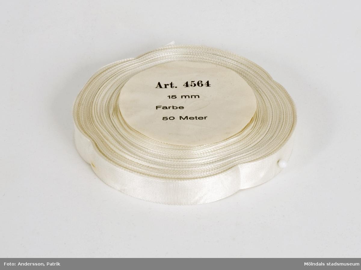 """Vitt sidenband på rulle, som använts vid tillverkningen av produkter på Kuverteringen, Papyrus. I mitten, papprulle som stöd, med sidor klädda i papper med texten """"Art. 4564, 15 mm, Farbe, 50 meter""""."""