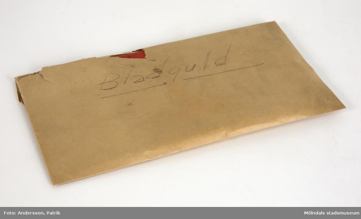 """Bladguld i silkespapper, förvaras i pappfodral. 1: Röd pappärm (160x117 mm), textilklädd. Innehåller två små silkespappershäften, vari bladguldet ligger.2: Naturvitt papperkuvert (105x180 mm), som innehåller två små silkespappershäften, vari bladguldet ligger.3: De ovannämnda föremålen förvaras i ett avlångt, brunt kuvert, märkt """"Bladguld"""" med blyerts. Kuvertet är mycket skört."""