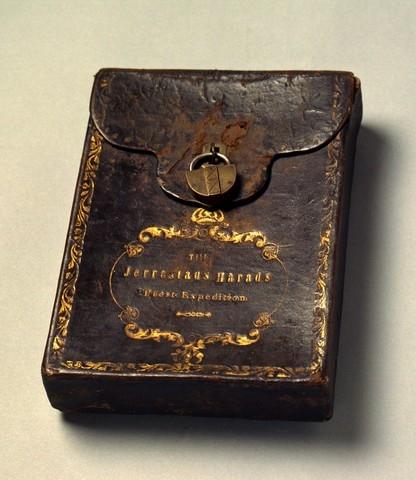 Klockarpostväska i form av ett låsbart (med hänglås) fodral. I fodralet förvaras en kvittensbok (PM 17200) från Simrishamns Pastors Expedition. På väskans framsida hänger i låsöglan ett litet hänglås i mässing och en till det tillhörande nyckel. Väskan som är i läder har en i guldsnitt broderad kant och text enligt signering/märkning inom en ornerad medaljong vilken överst kröns med kunglig krona, allt i guldsnitt.