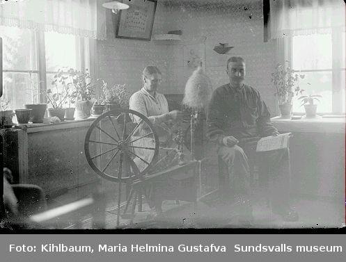 Bostadsinteriör, kvinner sitter vid spinnrock, man läser tidning.