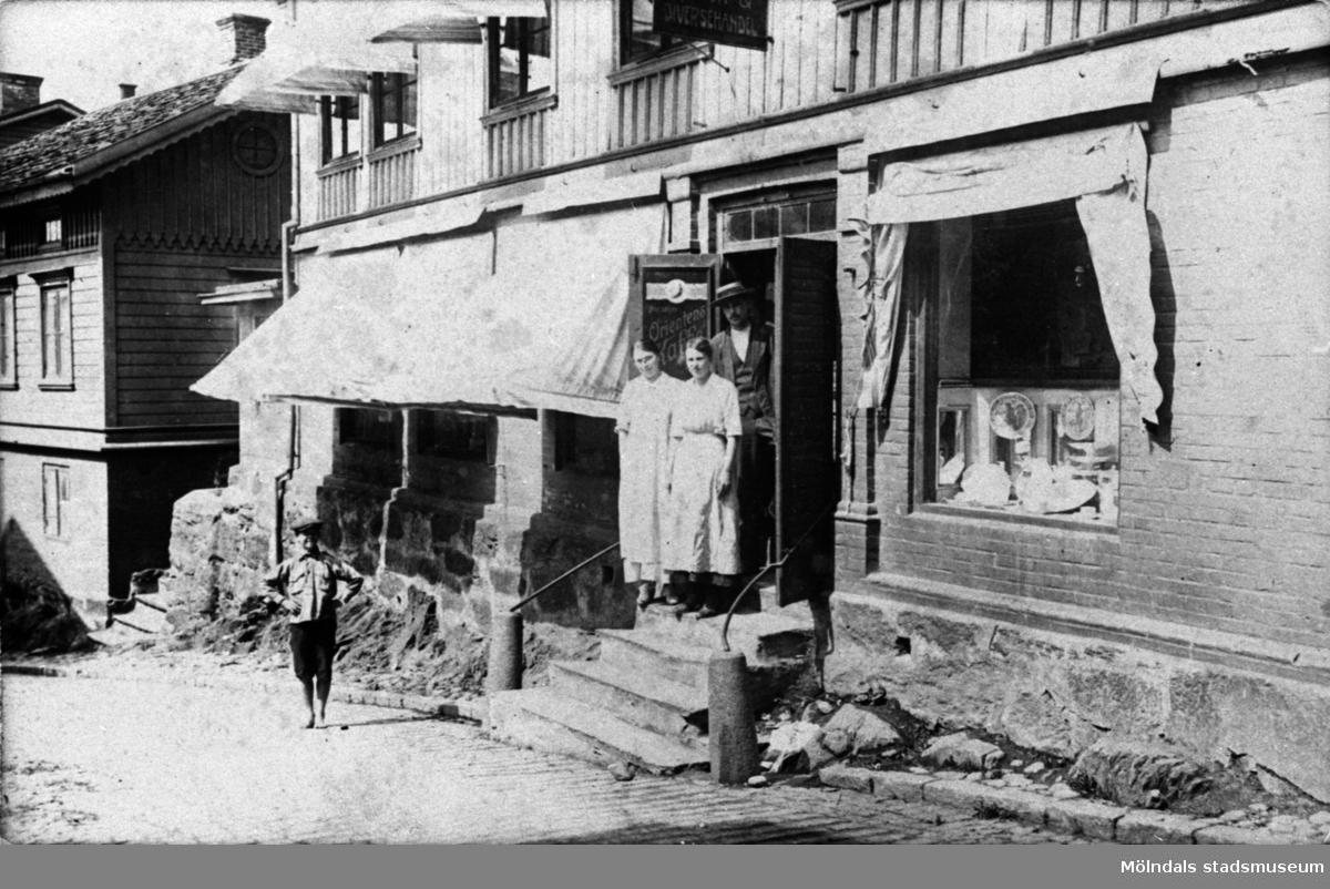 """Örns affär vid """"Kråkan"""" i Mölndal på 1910-talet. Vid ingången, på trappan står två kvinnor (troligen butiksbiträden) och en man. Nedanför står en pojke."""