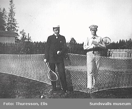 Två män vid tennisnät med tennisrackets i handen.