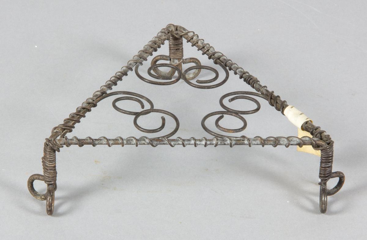 Pannställ, underlägg tillverkad av ståltråd. Hjärtmönstrat, trekantigt med uppböjda fötter.