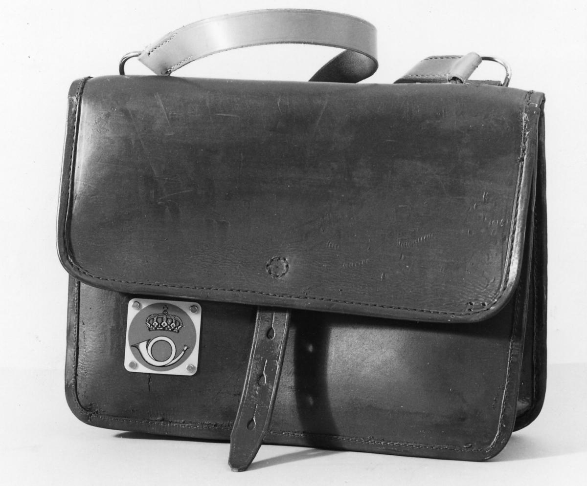 Postväska av läder med axelrem i läder. Skylt av plast med postsymbol modell 1937.