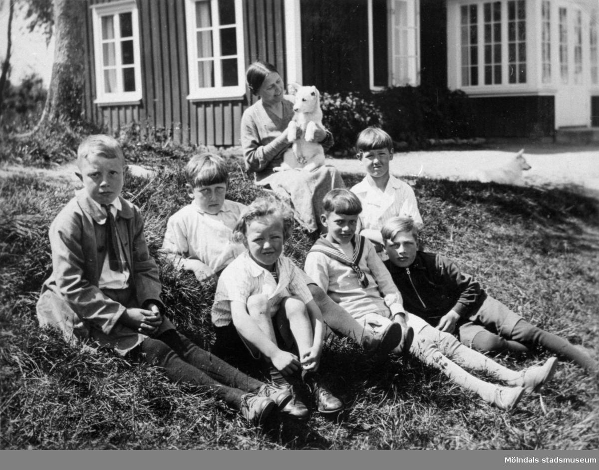 """Valdeborg Johansson med hund i famnen tillsammans med sina elever utanför skolan, våren 1934. Text på fotots baksida: """"Småfolk"""". Samma elever som på bild 1992_0007, 0008. Ur Valdeborg Johanssons fotoalbum."""