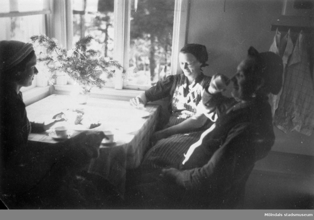 Sonja Svenssson, Albert Persson och Augusta Persson tar en kaffepaus runt köksbordet på Långö, 1950-talet.