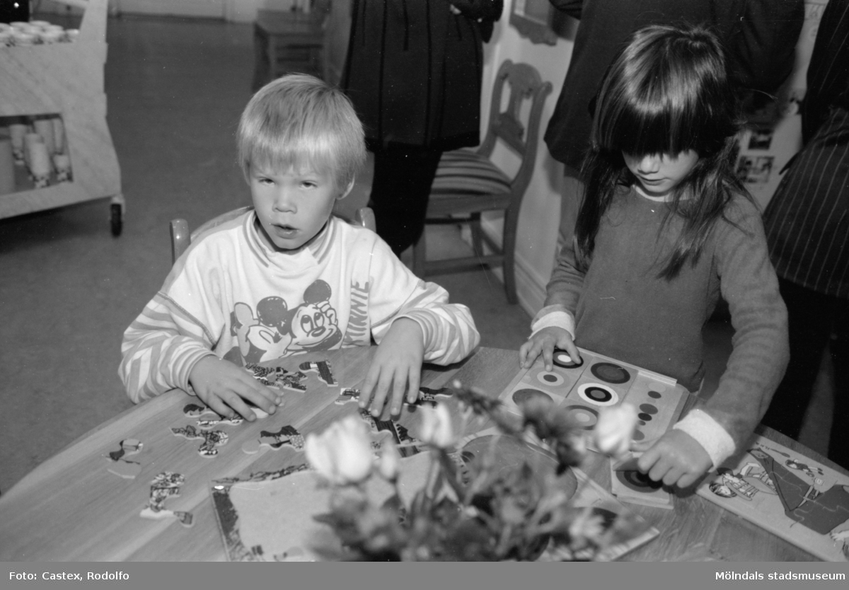 Två barn som sitter och pysslar vid ett bord. Utställningsvernissage av och om Katrinebergs daghem på Mölndals museum 1993-09-10.