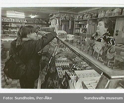 Fotodokumentation av Märta Persson, livsmedelsaffär i kv Mandeln 1, Majorsgatan 17, Sundsvall.1 juli 1922 övertog Märta Persson (gift Claésson) mjölk- och speceriaffären. Affärsnamnet blev hennes flicknamn. Fram till 1980-talets mitt arbetade hon dagligen i affären. Den förestås nu av dottern, Kerstin Sunding.