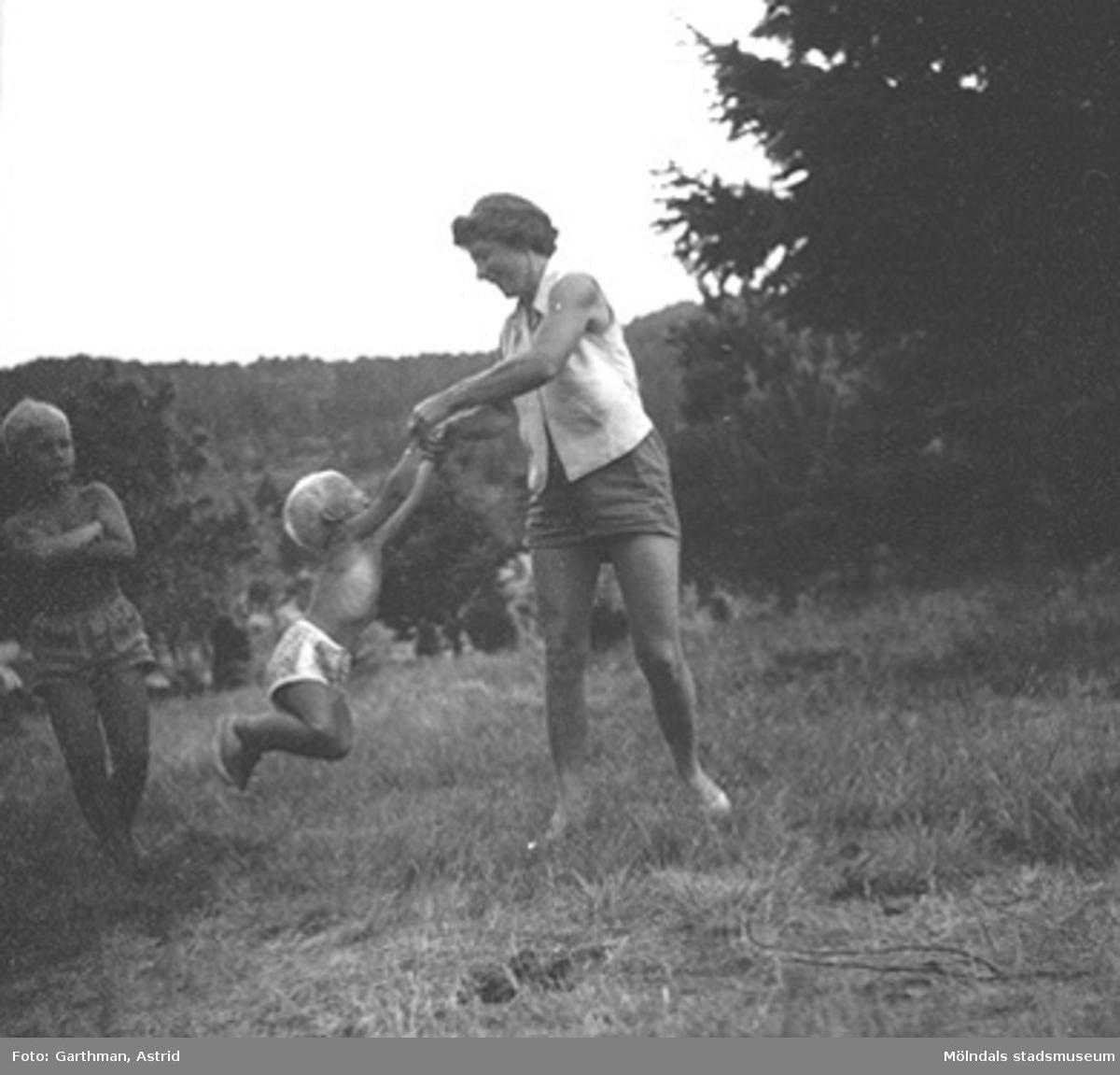Ulla Torgé svänger runt med sonen Olle Torgé i Mölndal, 1950-tal. Okänt barn tittar på. Vänner till familjen Garthman som är på besök.