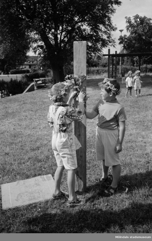 Två pojkar dekorerar en stående brädbit med blommor. Båda har blomsterkransar i håret. Johannes är vänd mot fotografen. Trudelutten, Katrinebergs daghem, 1992-93.