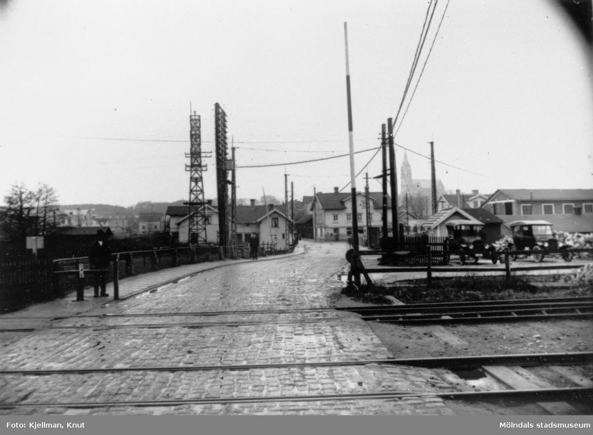Man ser Kvarnbygatan från järnvägsövergången fram mot Mölndalsbros vägkorsning Kvarnbygatan, Frölundagatan, Göteborgsvägen och Kungsbackavägen. 1910-1930-tal.