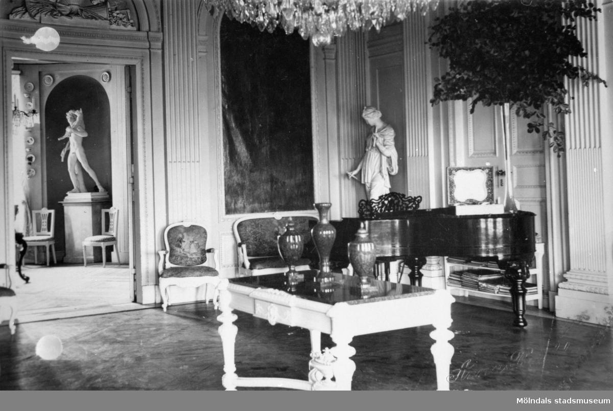"""Stora salongen på Gunnebo slott. Ett ljust, snidat bord med tre urnor stående ovanpå. I bakgrundens mitt står statyn """"Våren"""" (i nordost) av Gioacchino Frulli (1766-1801) och en flygel. Till vänster i bild syns entrén till matsalen."""
