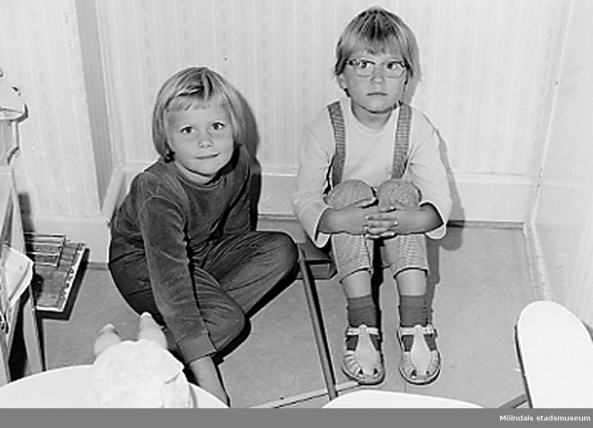 Två flickor som sitter på golvet framför ett element. Holtermanska daghemmet 1953.