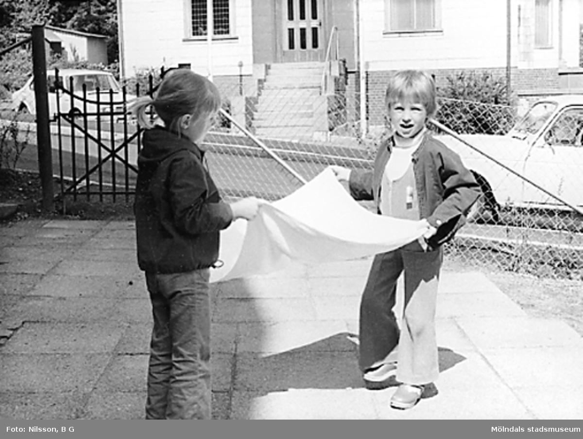 Två barn som skakar ett ljust tygstycke utanför Holtermanska daghemmet juni 1973.