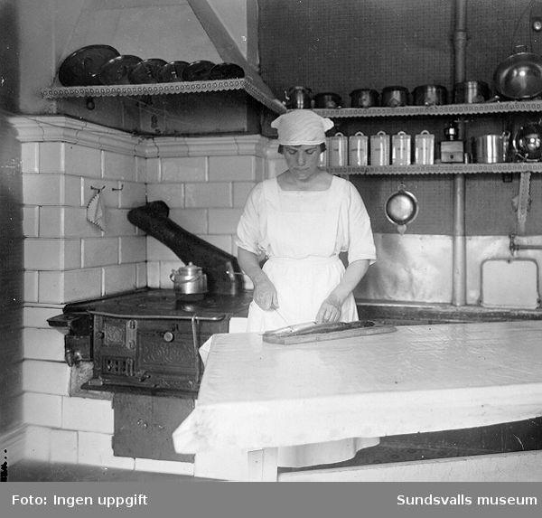 Kvinna som filear fisk i köket. Vedspis i bakgrunden