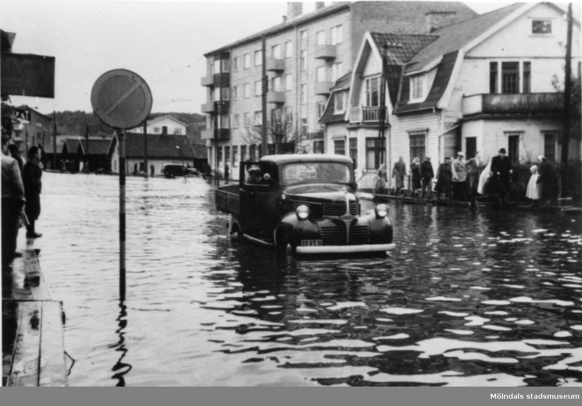 Översvämning på Göteborgsvägen, 1950-tal. Från vänster ses Göteborgsvägen 7 (Såpan) och 9. Längre bort ses Ekmans gård på nuvarande Stadshusplatsen. En lätt lastbil forcerar vattenmassorna.