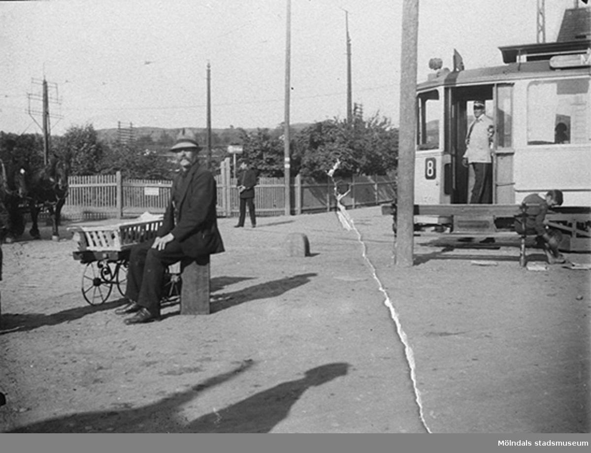 Konduktör står i öppning till spårvagn med linjenummer 8 (Mölndalsvagnen), 1910-tal. Till höger sitter en man på en stenpelare. Oklart var bilden är tagen.