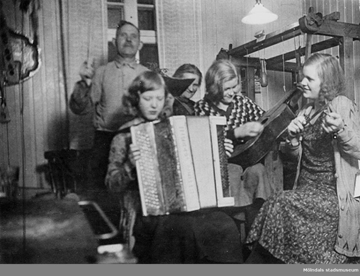 Tre flickor spelar dragspel och gitarr, i bakgrunden står föräldrarna. Snett till höger står en vävstol. Mölndal, 1930-tal.