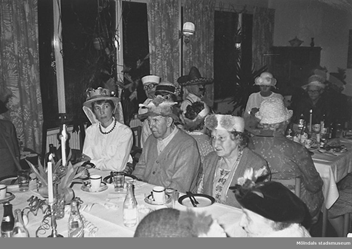 Personer iklädda hattar sitter vid långbord och har fikat klart. Okänt årtal.