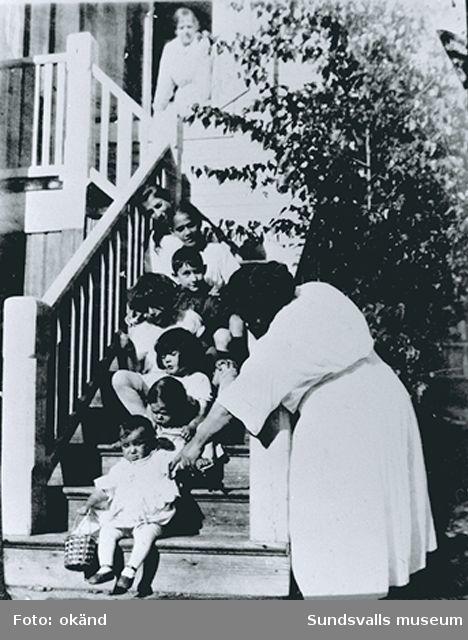 Iván Grünewald sitter som tredje barnet nerifrån i trappan bland sina kusiner, Kummelnäs, Värmdö. T h Isaac Grünewalds syster Dora som passade Iván på 1910-talet.