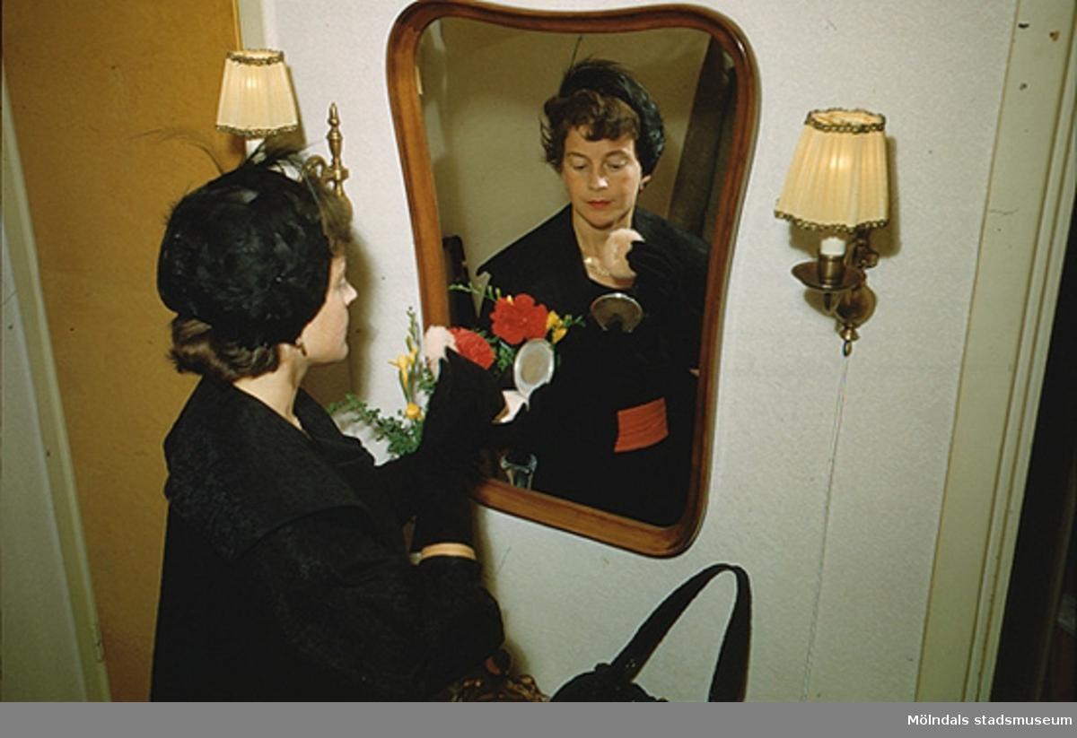 Margit pudrar näsan framför spegeln, år 1955. Hatten finns i Mölndals stadsmuseums samlingar med invnr. 03333.