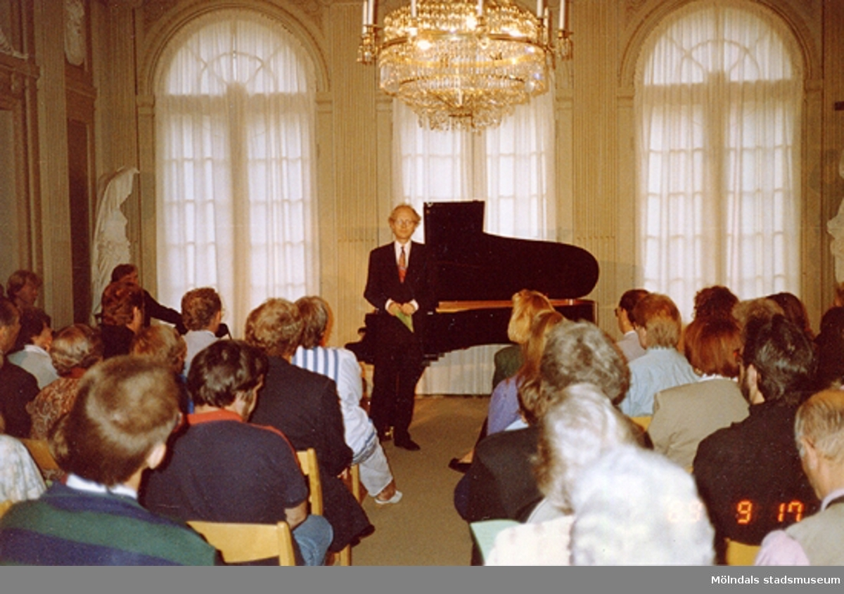 En musikkonsert inne på slottet. En man står vid ett piano.