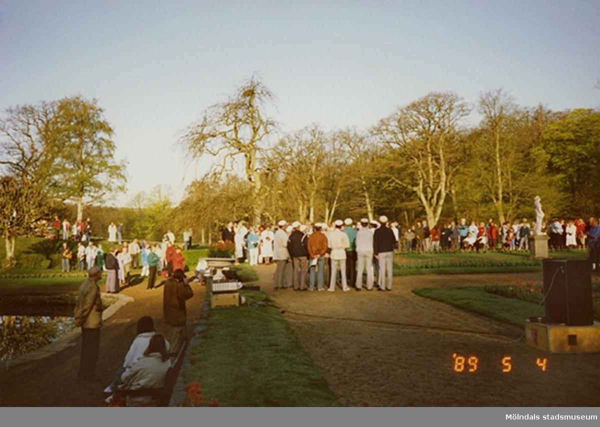 Besökare vid dammen som lyssnar till sjungande studenter.