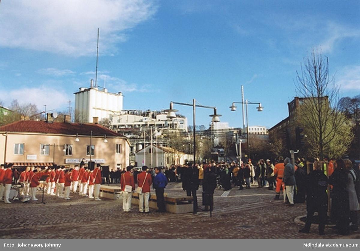 Gamla torget i Mölndal den 22:a november 2001. Folk lyssnar till invigningstal och Mölndals paradorkester underhåller.Invigning efter omläggning och stenläggning av torget. I bakgrunden syns Soabs fabriker.