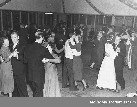 """Dans i färgeriet på Luciadagen. Detta var en årlig tradition och en av arbetslokalerna gjordes då om till dansgolv. Slutet av 1940-talet.Hösten 1944 flydde 32.000 estländare från kriget i Estland till Sverige. Ett sextiotal personer tog jobb på August Werners textilfabrik i Lindome. Kvinnorna arbetade i spinneriet och männen i färgeriet.Mer information finns i uppsatsen """"Estländska textilarbetare i Lindome"""" som finns i Mölndals stadsmuseums interna arkiv."""