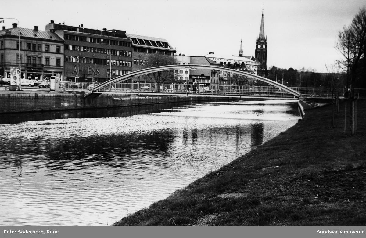 """""""Puckelbron"""" med plan gångbana. Bron ersatte 1980 den äldre bågformade som utgjorde ständiga halkproblem på vintrarna. Ersattes 1989 av en ny betongbro."""