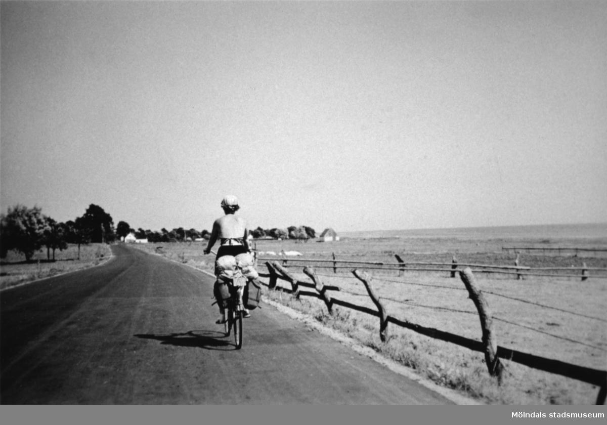 En person cyklar på en landsväg cirka 1930.