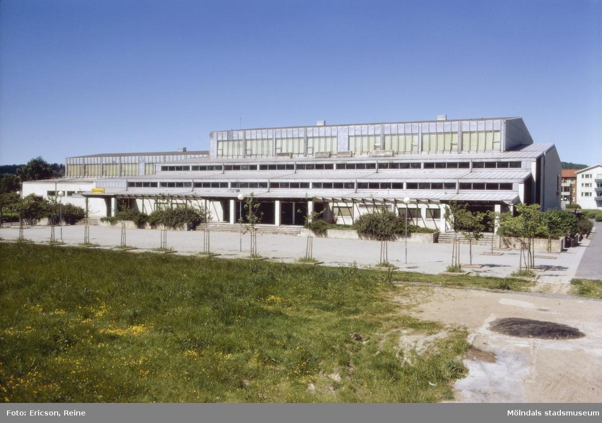 """Idrottshuset i Mölndal.  Under hösten 1965 öppnades det nya idrottshuset, som är beläget väster om kyrkan utmed Toltorpsgatan.  Idrottshuset betjänar den frivilliga gymnastiken och idrotten inom kommunen och tillgodoser även de angränsande skolornas behov av gymnastiklokaler.  Byggnaden innehåller tävlingshall med plats för 1.500 åskådare samt en något mindre träningshall. Bada hallarna kan genom """"ridåer"""" uppdelas så, att fyra gymnastiksalar erhålles.  I en undre våning finns dessutom lokaler för bl.a. brottning, judo, tyngdlyftning, bordtennis, rytmisk gymnastik, dans, balett samt en bowlinghall med 8 banor.  Ett stort antal idrottsintresserade tränar varje dag i idrottshuset.  Dessutom finns ytterligare fyra idrottshallar inom kommunen nämligen: Sörgårdshallen, Åbyhallen, Kvarnbyhallen och den nybyggda Almåshallen."""