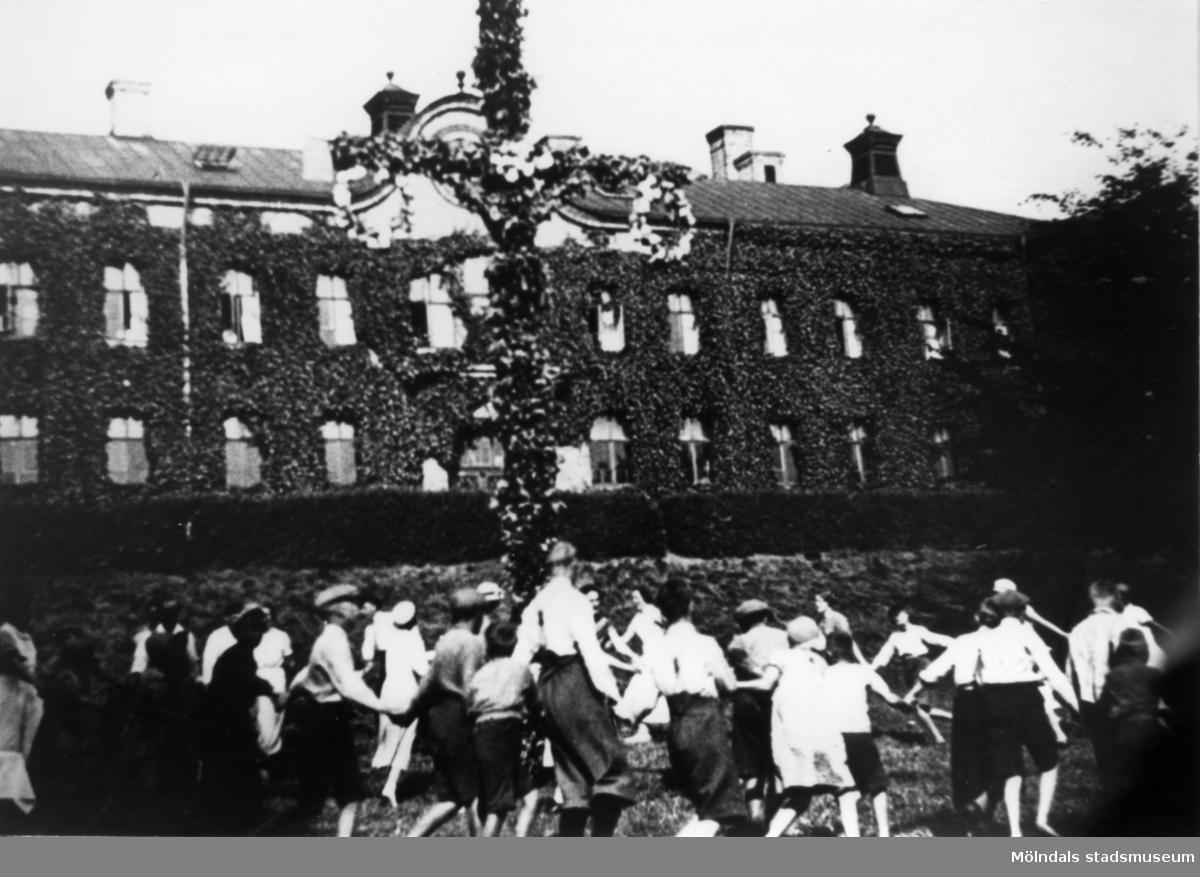 Midsommarfirande vid Streteredshemmet i Kållered, 1930-tal. Stora skolan bakom staketet.