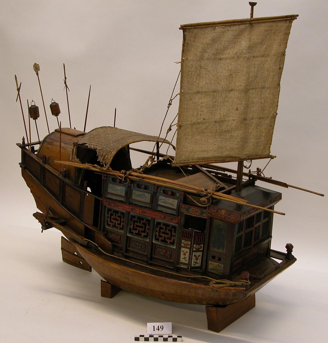Chinesisk Champon, en offentlig djonk använd av höga ämbetsmän under resa. Modell av trä, fernissad och målad i olika färger, tacklad och inredd, med en mast med segel, samt ett solskydd.