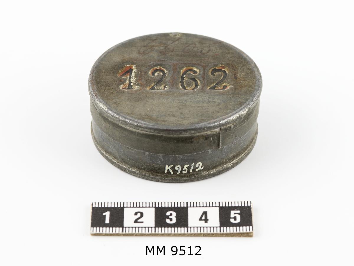 Avlöningsask av bleckplåt. Rund. Märkt på locket: Nr 1262, ifyllt med svart färg,samt skrivet med bläck: 6605.