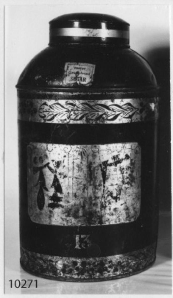 Burk, te-. Engelsk tillverkning. Cylinderformad, avsmalnad upptill med en kort hals, med lock. Svartmålad med kinainspirerade gulddekor. Märkt: 13 i guld. Text på en oval platta: Edvard Maund Shopfittings and Tradeutensils 28. Tover Hill, London. Tidigt 1800-tal.