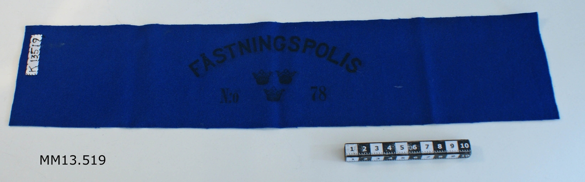 Armbindel. Färg: blå. Märkning i svart: FÄSTNINGSPOLIS NR 78. Tre st. kronstämplar.