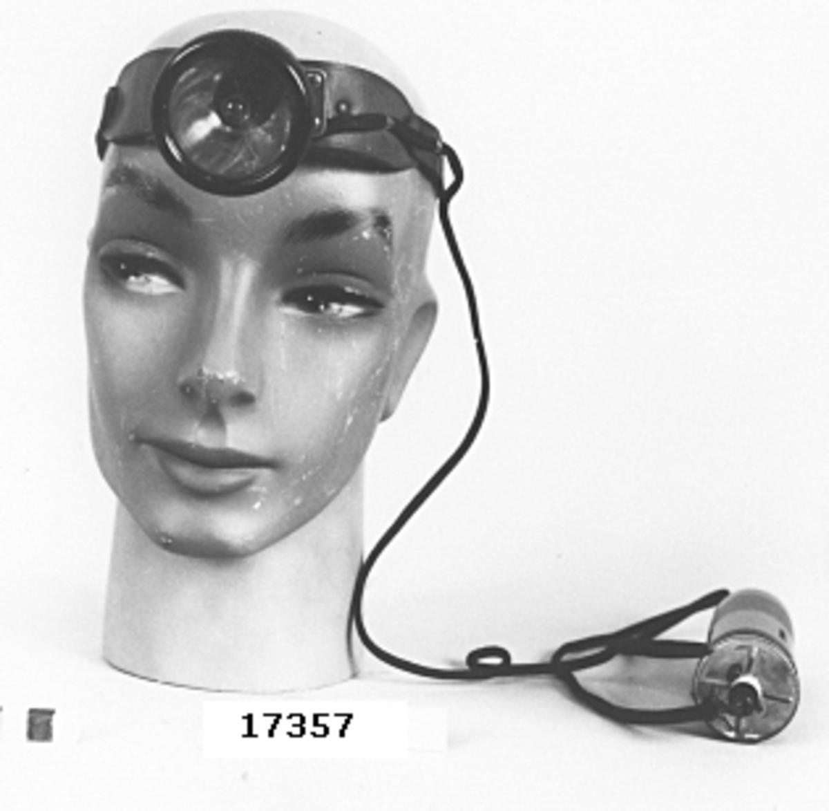 """Pannlampa bestående av justerbar läderrem (B= 20 mm) avsedd att fästas runt huvudet. I pannan sitter en lampa med hölje av rödmamorerad bakelit försedd med liten glödlampa, typ till ficklampa. Från lampan utgår en klädd ledning till en batterihylsa, också av rödmamorerad bakelit (D= 38 mm, L= 133 mm). Märkt: """"Zeiler"""" samt """"made in Germany"""". På insidan av pannbandet vid lampan sitter orange gummi."""