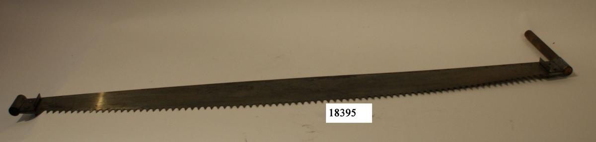 Stocksåg av stål, ena sidan rak med trekantiga tänder, andra sidan svagt böjd. Ändarna böjda till tunnlar och nitad på sågen. Försedd med handtag av trä, rundstav, på ena sidan.